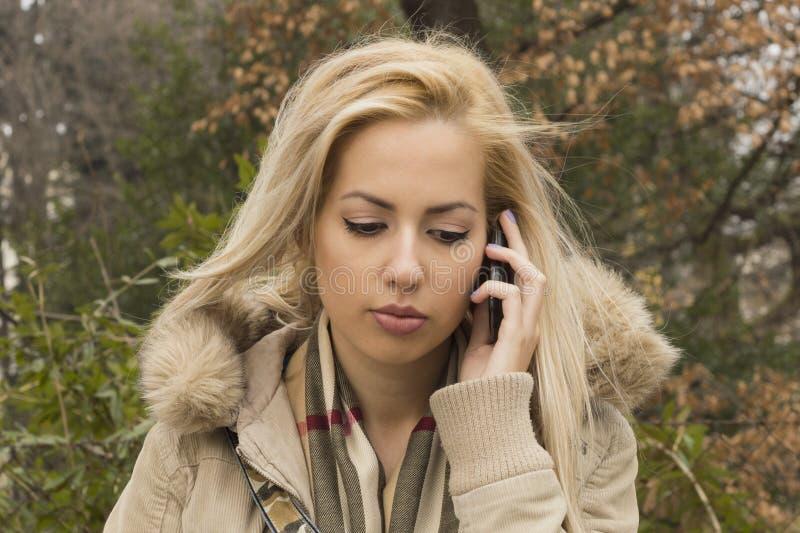 Ledsen flicka som talar på mobiltelefonen royaltyfria bilder