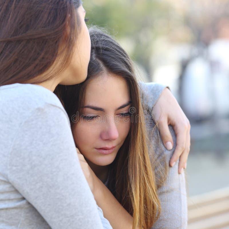 Ledsen flickagråt och en vän som tröstar henne arkivfoton