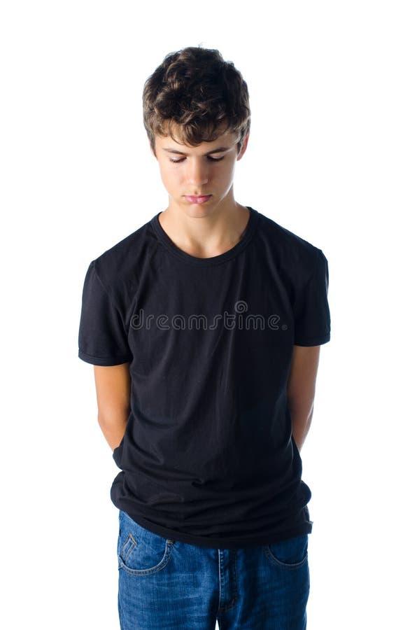 Ledsen grundad tonåringpojke se ner royaltyfri fotografi