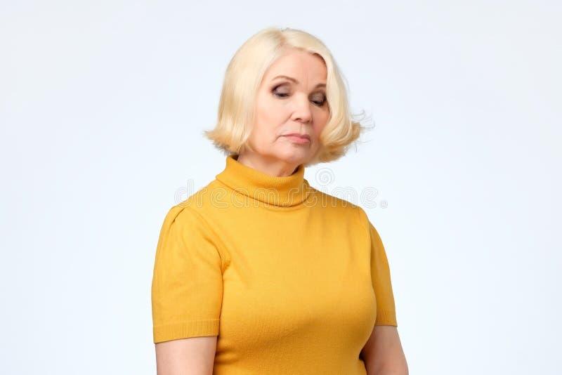 Ledsen hög blond kvinna i gul kläder royaltyfria bilder