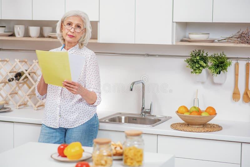 Ledsen hög hemmafru som analyserar nytto- räkningar royaltyfri foto