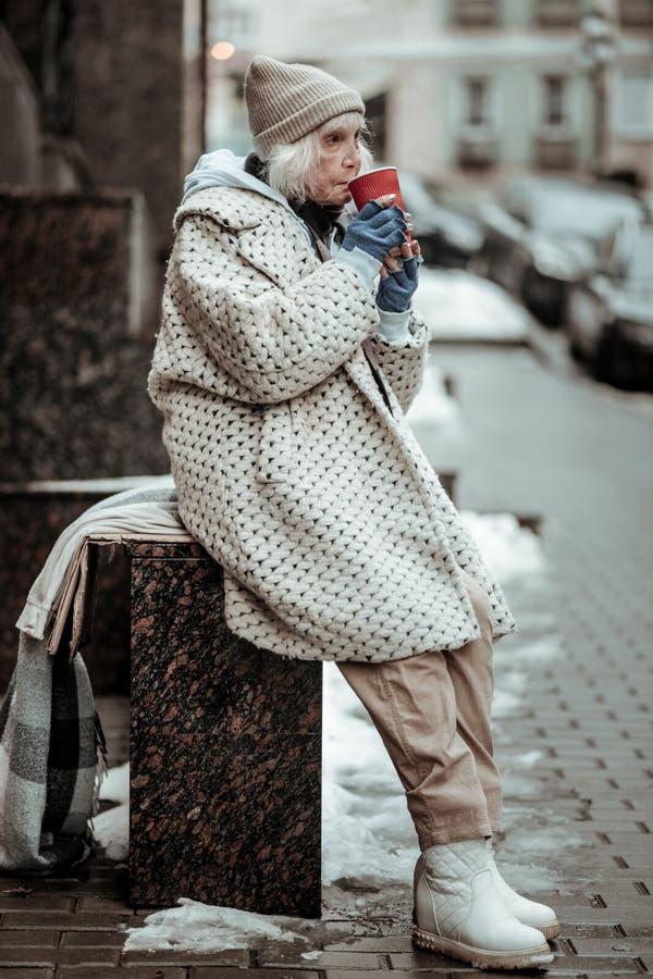 Ledsen hög kvinna som har mycket varmt te royaltyfria foton