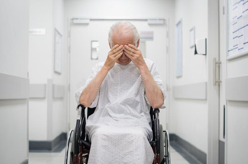 Ledsen hög man på rullstolen royaltyfri fotografi