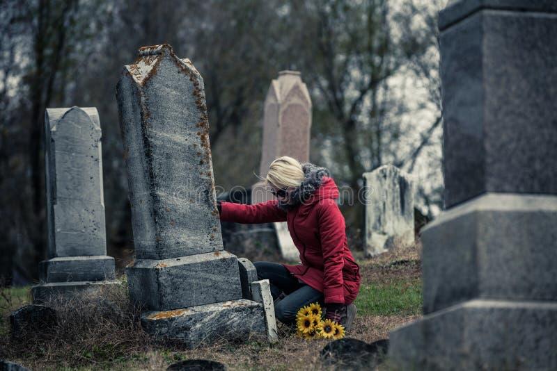 Ledsen kvinna, i att sörja tryckande på som älskas ens gravsten royaltyfri fotografi