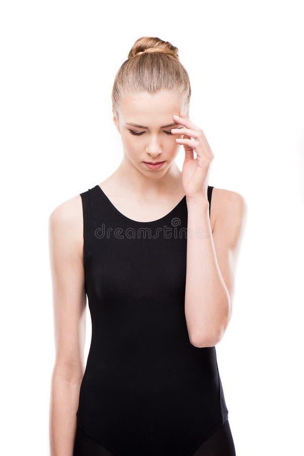 Ledsen kvinna i body med huvudvärken och stängda ögon som trycker på hennes huvud arkivbild