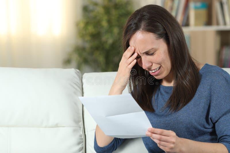 Ledsen kvinna som hemma läser ett brev på en soffa royaltyfri foto