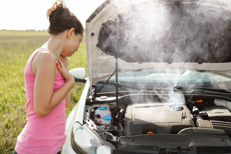 Ledsen kvinna som ner ser den brutna bilmotorn royaltyfria foton