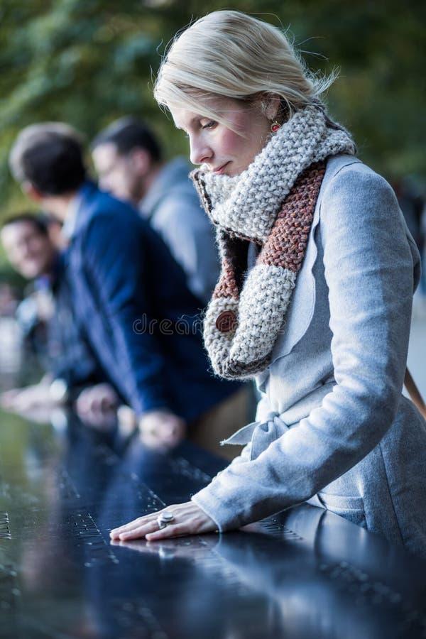 Ledsen kvinna som ser namnen av World Trade Centerminnesmärken arkivfoton