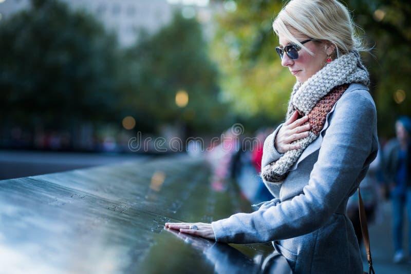 Ledsen kvinna som ser namnen av World Trade Centerminnesmärken royaltyfri bild