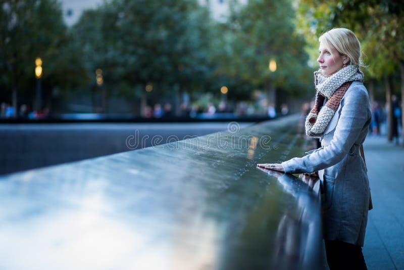 Ledsen kvinna som ser namnen av World Trade Centerminnesmärken royaltyfria bilder