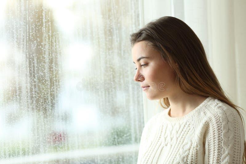 Ledsen kvinna som ser till och med ett fönster om den regniga dagen fotografering för bildbyråer