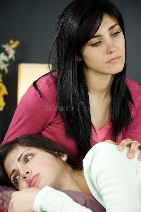 Ledsen kvinna som sitter på deprimerad sängkänsla ha problemcloseupen arkivbild