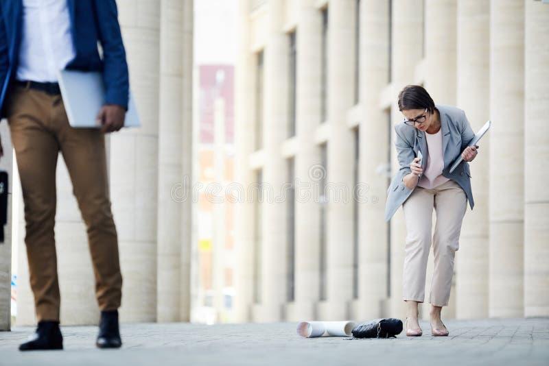 Ledsen kvinna som tappar material nära kontor arkivbilder