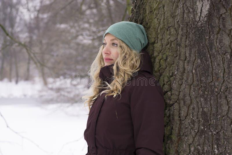 Ledsen kvinnabenägenhet mot träd i vinter royaltyfria foton
