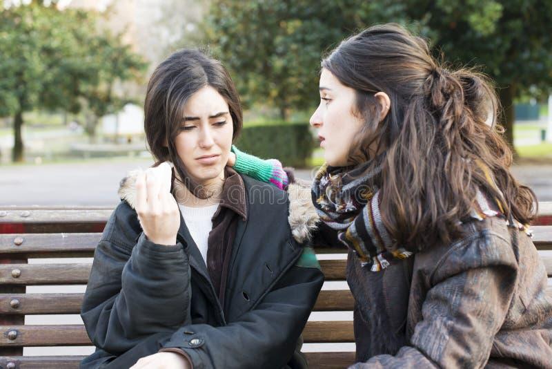 Ledsen kvinnagråt och vän som conforting i parkera arkivfoto