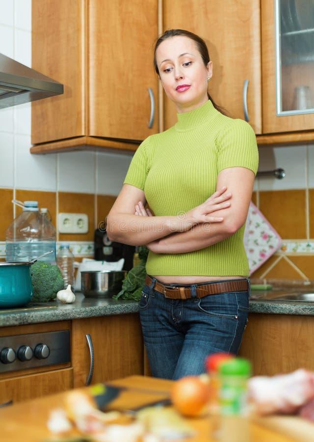 Ledsen kvinnlig som tröttas för att laga mat arkivbild