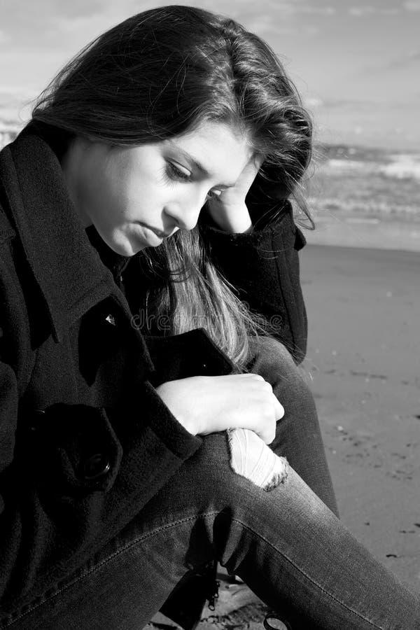 Ledsen kvinnlig tonåring som framme sitter av havet royaltyfri foto