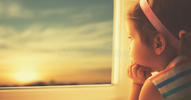 Ledsen liten flicka för barn som ut ser fönstret på solnedgången royaltyfri bild