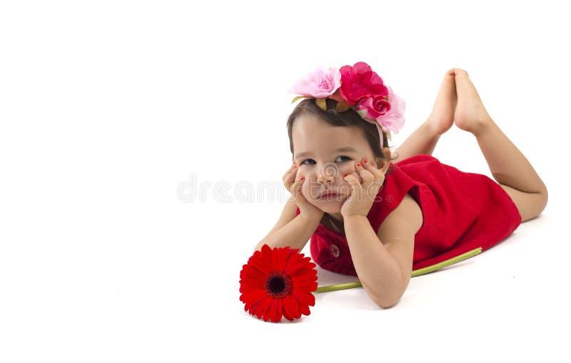 Ledsen liten flicka med den röda blomman royaltyfri bild