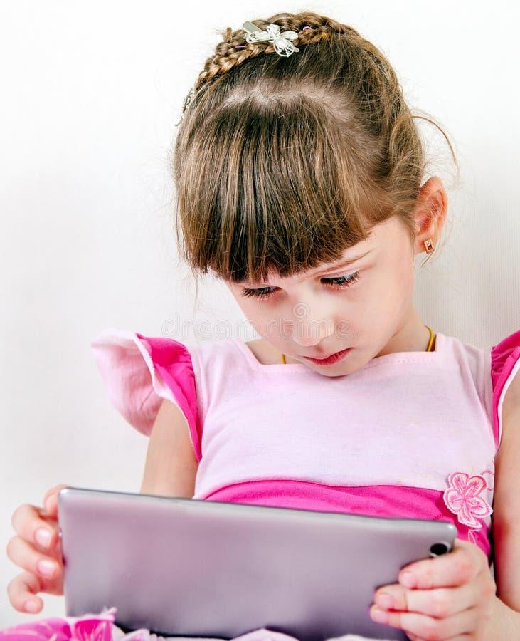 Ledsen liten flicka med en minnestavla royaltyfria bilder