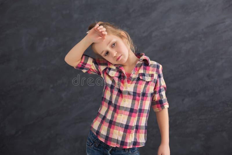 Ledsen liten flicka som poserar på grå bakgrund arkivfoton