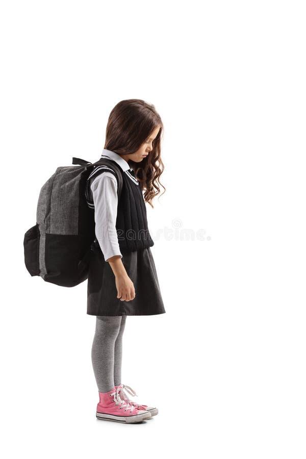 Ledsen liten skolflicka med en ryggsäck royaltyfri foto