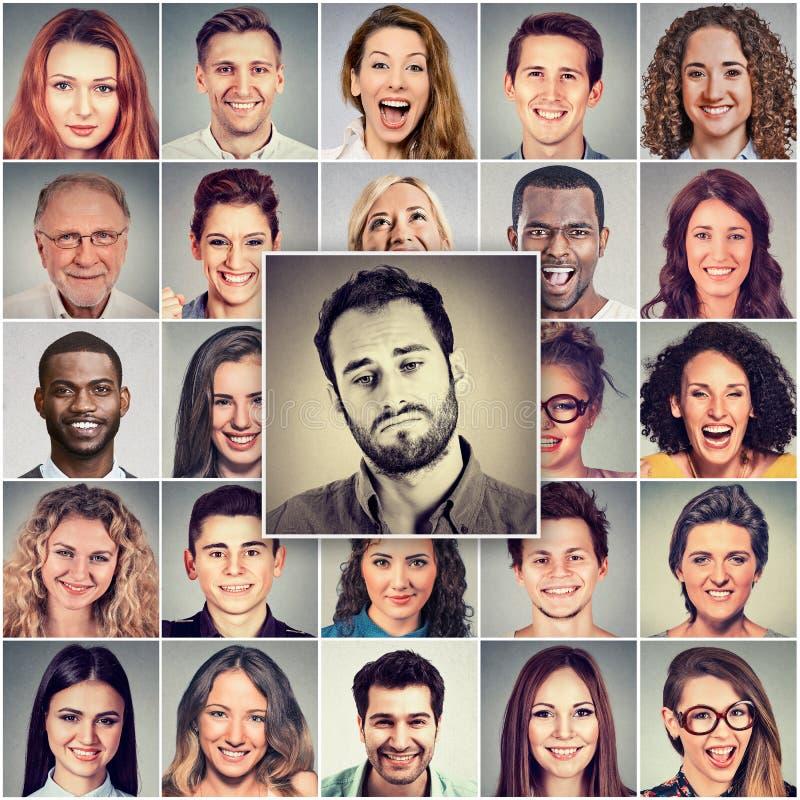 Ledsen man bland gruppen av lyckligt folk royaltyfri bild