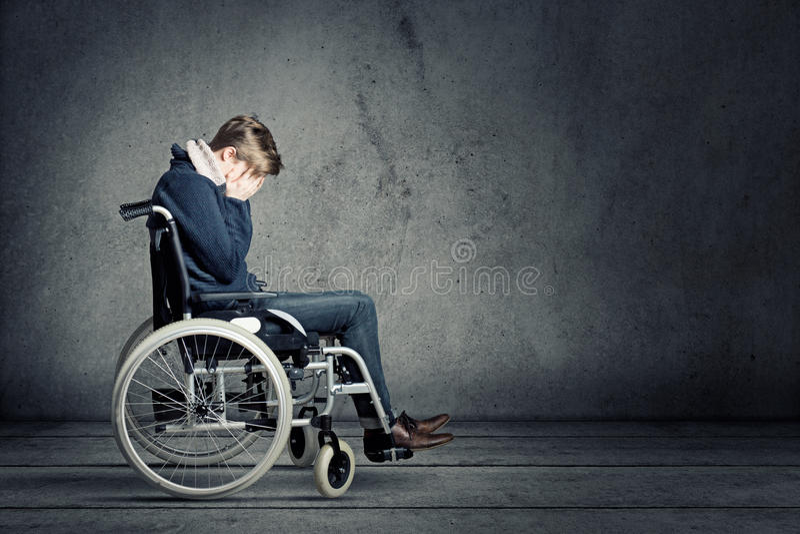 Ledsen man i rullstol arkivbild