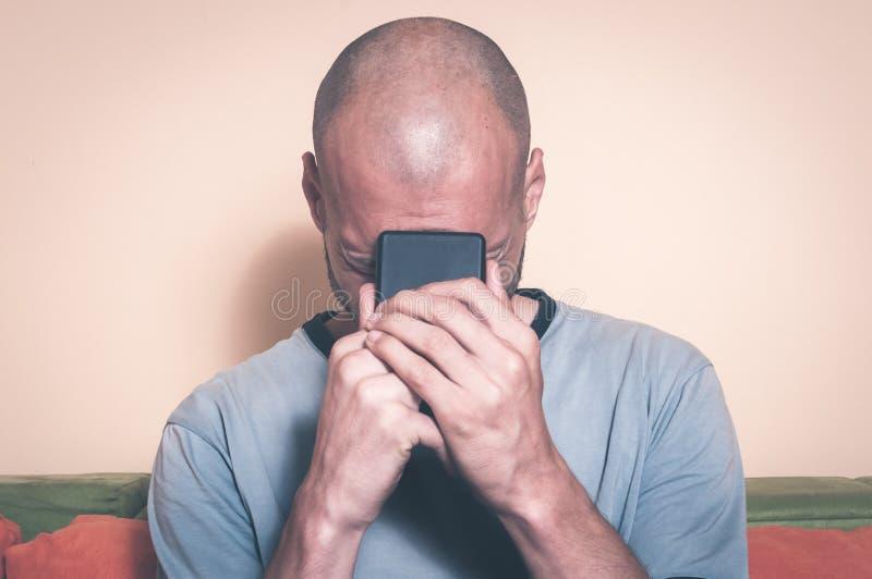 Ledsen man som rymmer hans mobiltelefon i hans händer, och skrik, därför att hans flickvän bryter upp med honom över textmeddelan arkivbild