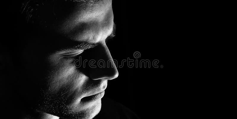 Ledsen manprofil, mörk grabbman i fördjupningen, svartvit allvarlig blick royaltyfri foto