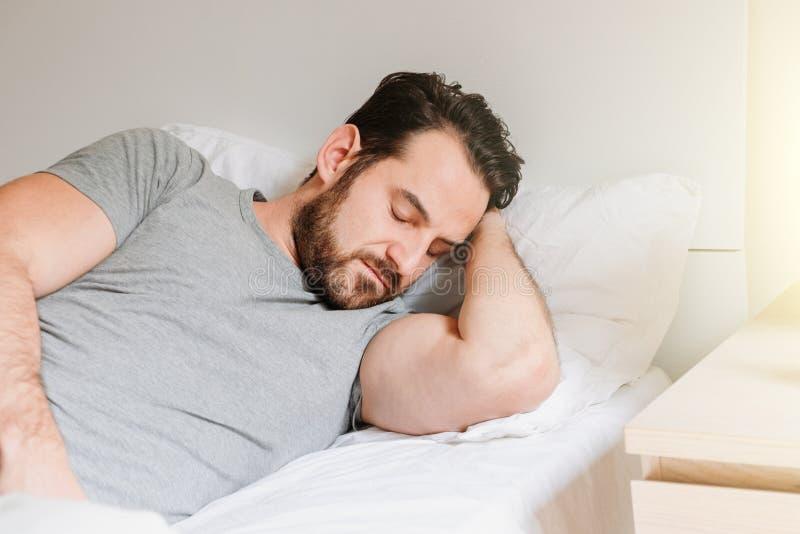 Ledsen manstående som hemma ligger i hans säng arkivfoto