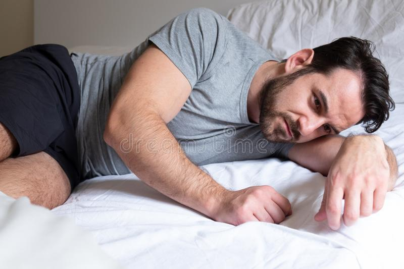 Ledsen manstående som hemma ligger i hans säng arkivbild