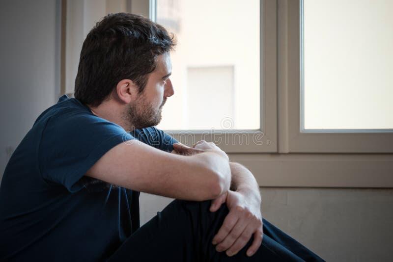 Ledsen manstående som ser ut ur fönster royaltyfri bild