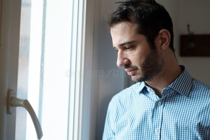 Ledsen manstående som ser ut ur fönstret arkivbild