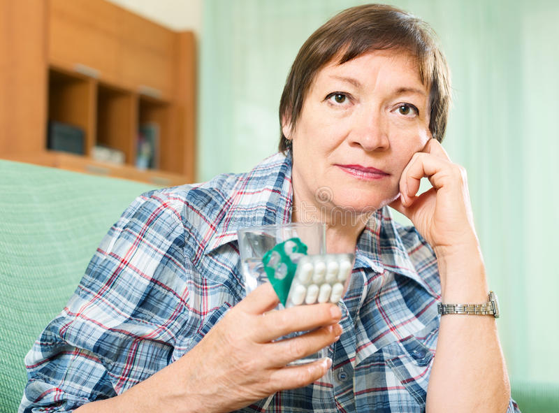 Ledsen mogen kvinna med preventivpillerar och exponeringsglas av vatten royaltyfria foton