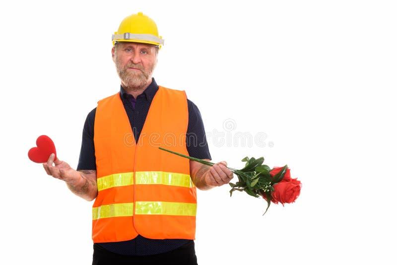 Ledsen mogen skäggig manbyggnadsarbetare som rymmer röd hjärta och arkivfoton
