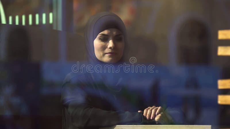 Ledsen muslimsk dam i traditionell hijab i kafé som tänker om hemmet, emigration arkivbilder