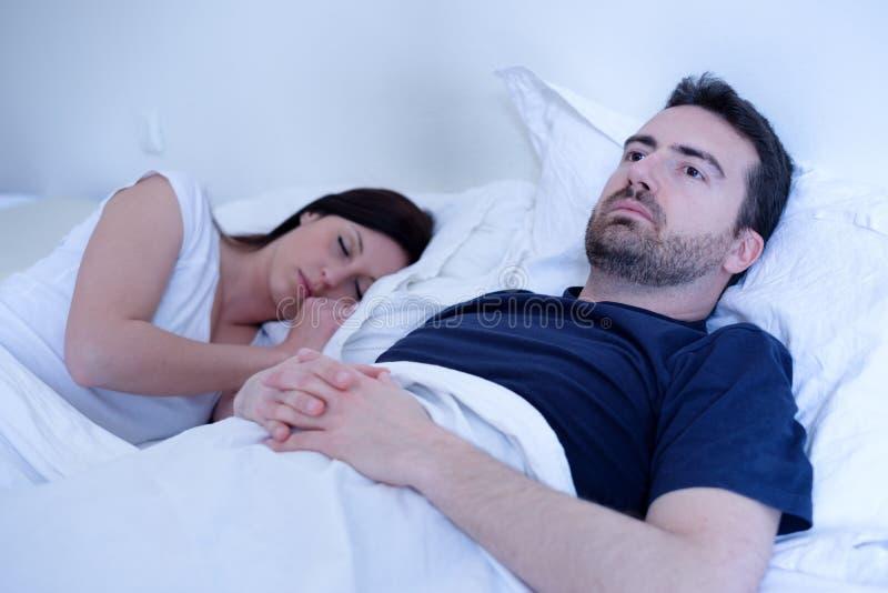 Ledsen och deprimerad man som ligger i sängen med frun fotografering för bildbyråer