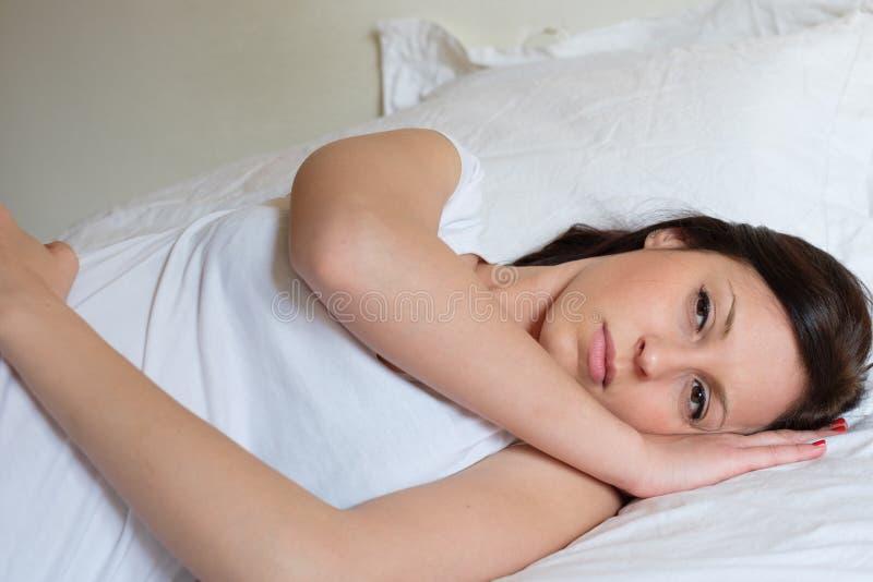 Ledsen och ensam kvinna som ligger i hennes säng royaltyfri foto