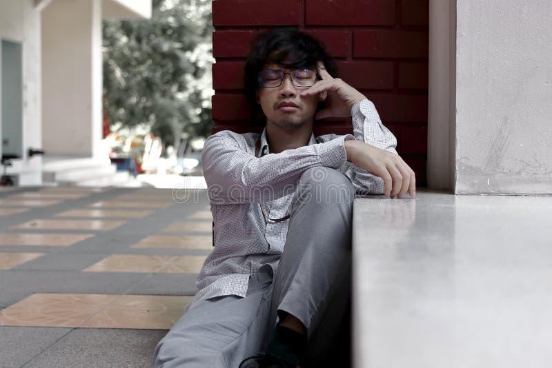 Ledsen och för ångest ung asiatisk man som lider från sträng fördjupning arkivbilder
