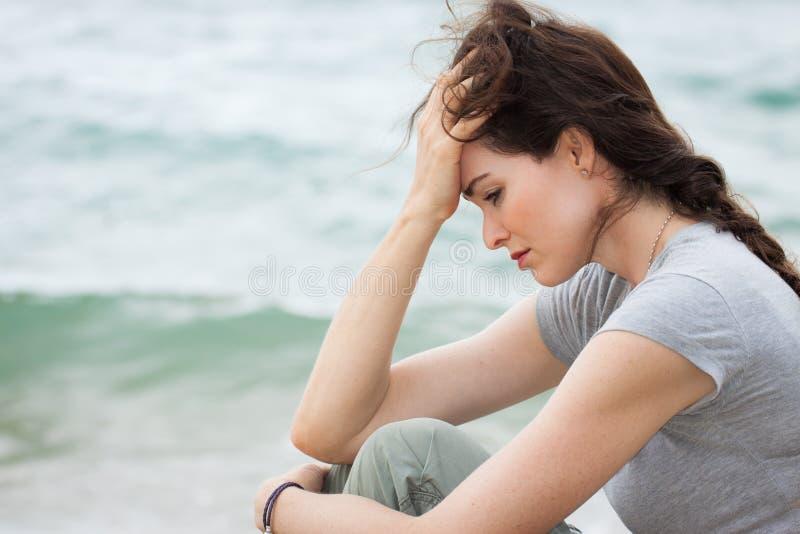 Ledsen och uppriven kvinna djupt i tanke arkivfoto
