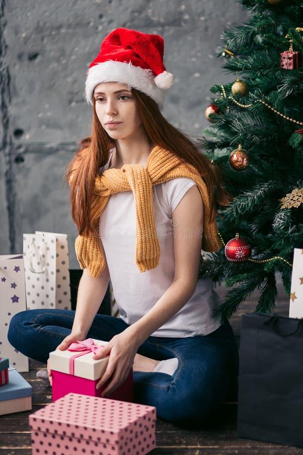 Ledsen olycklig flicka som framme sitter av det Cristmas trädet royaltyfri foto