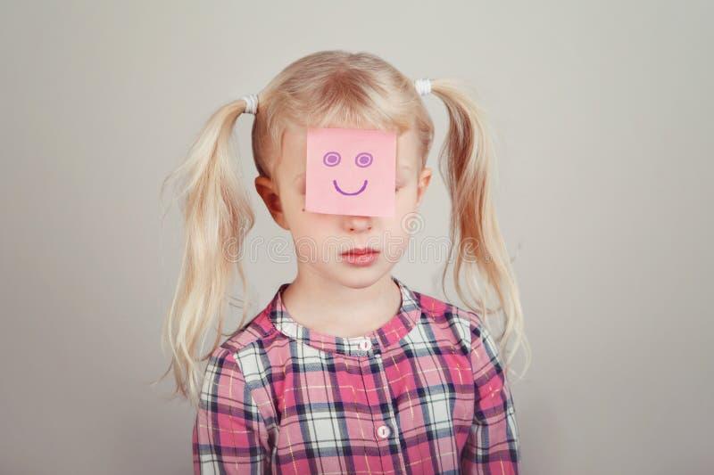 Ledsen olycklig vit blond Caucasian förskole- flicka med roligt klibbigt anmärkningspapper på hennes framsida arkivbild