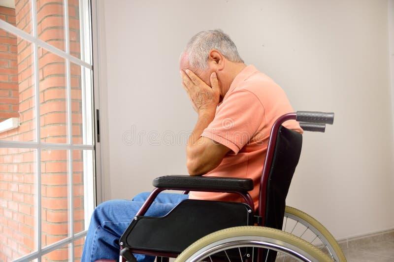 Ledsen pensionär i rullstol royaltyfri bild