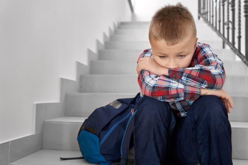 Ledsen pojke av grundskola f?r barn mellan 5 och 11 ?r som sitter p? trappuppg?ng fotografering för bildbyråer