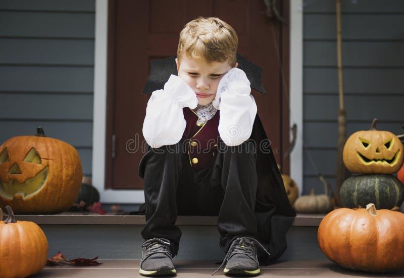 Ledsen pojke i en allhelgonaaftondräkt royaltyfri foto