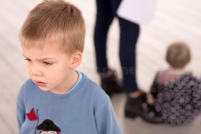 Ledsen pojke som är svartsjuk om att försummas av hans arkivfoton