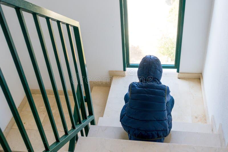 Ledsen pojke som bara sitter i hörnet av en trappuppgång arkivfoton