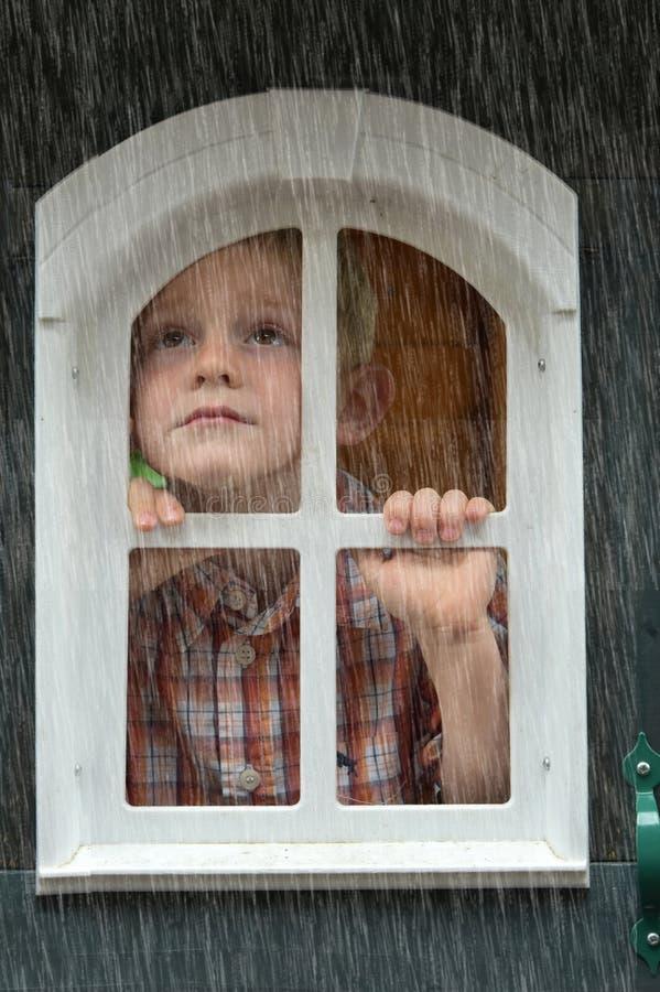 Ledsen pojke som ser regnet royaltyfria bilder