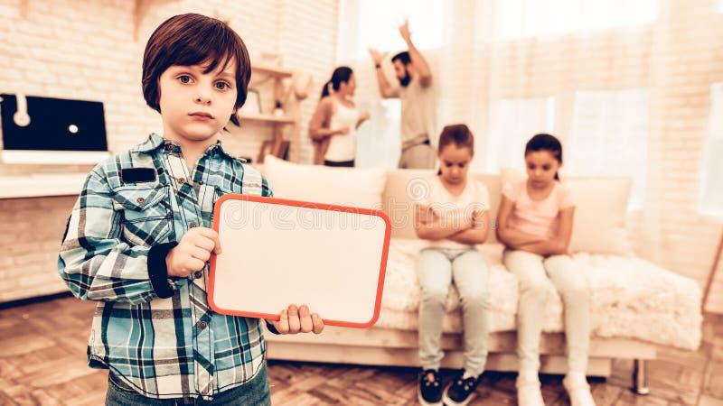 Ledsen pojke som visar tom brädefamiljbakgrund royaltyfri foto